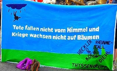 """Foto: Kundgebungstransparent vom Antikriegstag: """"Tote fallen nicht vom Himmel und Kriege wachsen nicht auf Bäumen"""""""
